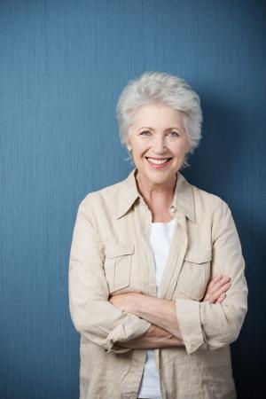 Stijlvolle moderne bejaarde vrouw stond lachend op de camera met gevouwen armen tegen een groene achtergrond