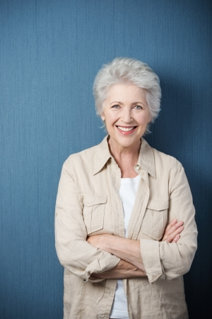 senior adult: Stylish modern elderly woman standing smiling at the camera with folded arms against a green background