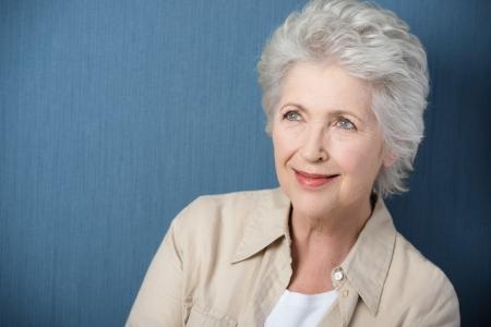 mujer pensativa: Hermosa mujer mayor so�ar despierto mirando hacia arriba con una suave sonrisa mientras recuerda recuerdos nost�lgicos