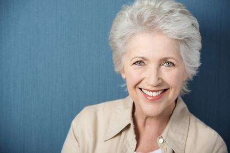 Copyspace と緑の背景とポーズをしながら、カメラを直接見て活気のある笑顔で美しくエレガントな老婦人