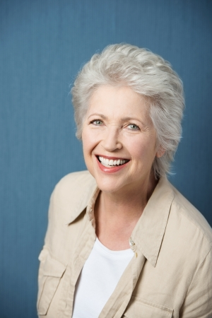 grey haired: Vivacious beautiful grey haired elderly woman full of vitality looking up at the camera with a beaming smile Stock Photo