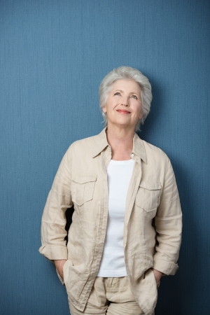 woman looking up: Nostalgic senior Caucasian woman wearing beige Casual shirt and pants and a white T-shirt, standing with her arms in her pockets with a blank chalkboard behind