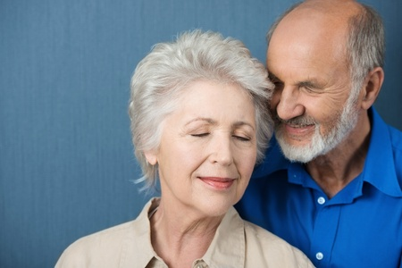 Elderly couple share a tender moment of love as they stand close together with their eyes closed in contentment and bliss