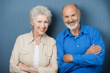 Confident elderly couple with folded arms standing side by side smiling at the camera against a green background