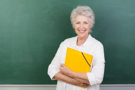 school teacher: Horizontal portrait of a Caucasian cheerful female senior teacher holding a yellow file with a blank chalkboard behind