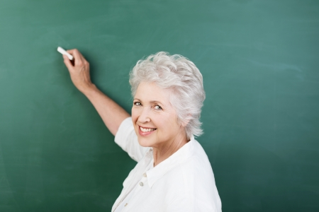 Senior woman writing on a blank chalkboard during a college class or business presentation turning to look back and smile at the camera photo