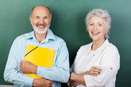 councilor: Confident happy senior couple standing with folded arms clutching a bright yellow folder Stock Photo