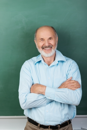Vertical portrait of Confident expert teacher looking at camera while sitting with arms folded with a blank chalkboard behind