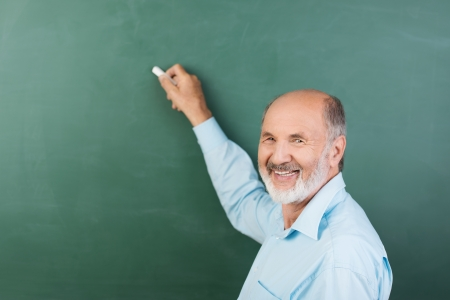 Elderly man with a friendly smile writing on a blank chalkboard during a business presentation or while teaching class at college photo