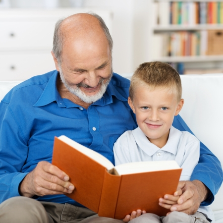 Grandfather reading to his small grandson who is looking up to smile at the camera as they sit arm in arm close together on a sofa in the living room photo