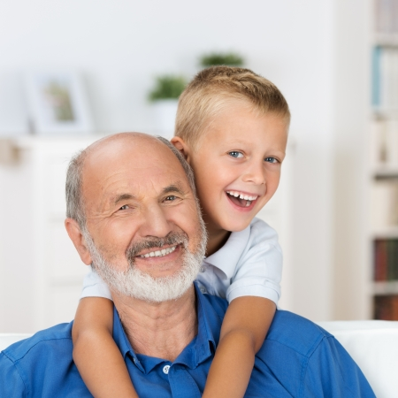 old man: Laughing grandfather with his grandson as they play together indoors in the living room with the cute young boy hugging him from behind Stock Photo