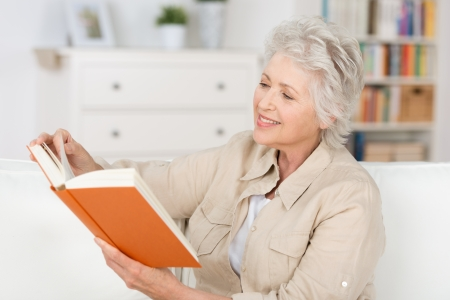 Attractive stylish elderly woman relaxing at home reading a book in her living room photo