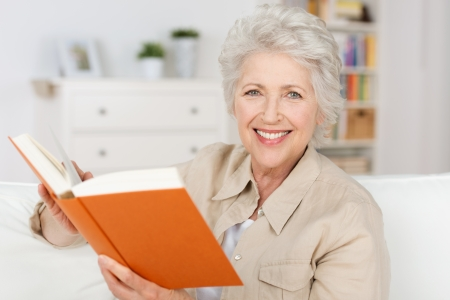 Smiling elderly lady reading a book while sitting in her living room pausing to look and smile at the camera