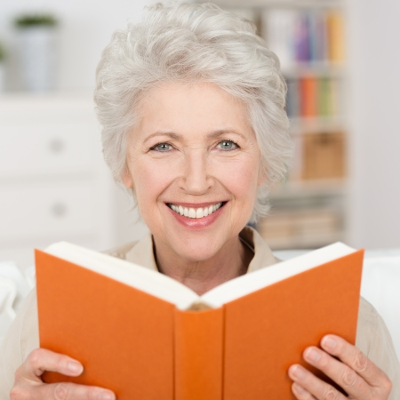 contented: Attractive grey haired senior woman with a lovely smile relaxing at home reading a book