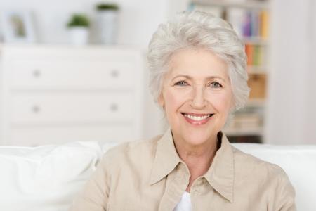 Caucasian senior beautiful woman enjoying the retirement home in her living room photo