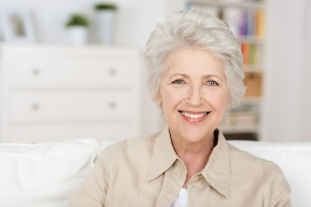 seniors homes: Caucasian senior beautiful woman enjoying the retirement home in her living room Stock Photo