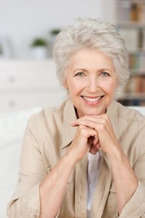 행복 웃는 수석 여자가 그녀의 손으로 그녀의 턱을 휴식과 직접 카메라를 찾고의 초상화를 닫습니다