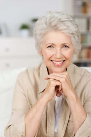 Close up portrait of a happy smiling senior woman resting her chin on her hands and looking directly at the camera photo