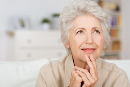 Doordachte senior dame zit thuis met haar vingers aan haar kin herinneringen en herinnerend goede herinneringen, close-up portret