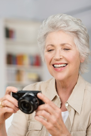 Vertical portrait of a happyCaucasian senior woman setting her compact camera Stock Photo - 21895846