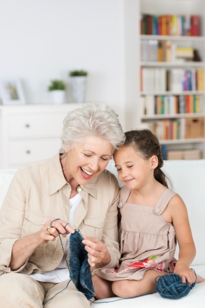grandparent: Senior lady teaching her granddaughter to knit as they relax together on the the sofa laughing together with enjoyment