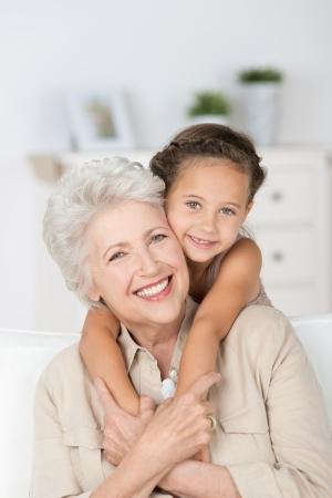 笑みを浮かべて愛情深い祖母とお互い愛情を与えてかわいい小さな孫娘抱擁、カメラに笑顔と幸せ