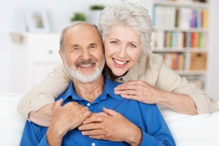 Aanhankelijk bejaarde echtpaar met prachtige stralend vriendelijke glimlach zich samen in een innige omhelzing in hun woonkamer Stockfoto