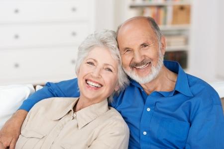 Romantisch senior paar zitten dicht bij elkaar op een bank in het huis gelukkig lachend op de camera