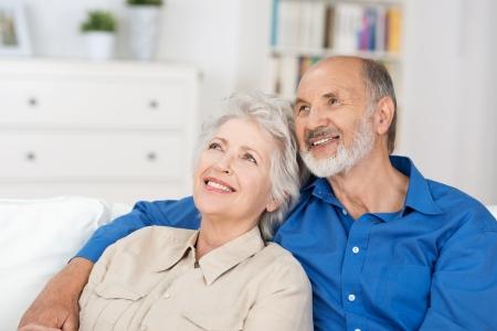 jubilados: Contento pareja de ancianos sentados en un estrecho abrazo en su sala de estar recordando y recordando recuerdos nostálgicos felices