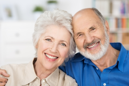 Affectionate happy retired couple with their heads together in a close embrace smiling at the camera photo