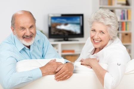 pareja viendo television: Feliz amigable pareja de ancianos de relax en su sala de estar en frente de la televisión de inflexión de sonreír a la cámara sobre el respaldo del sofá