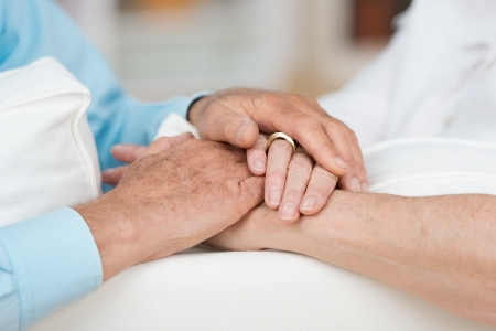 clasped: Sentimental conceptual image of love, commitment and support between two elderly people as they tenderly hold hands, close up view