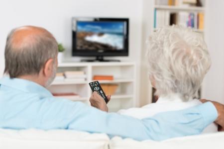 pareja viendo television: Pareja de ancianos viendo la televisión cómodamente sentados en un sofá de espaldas a la cámara que sostiene el control remoto