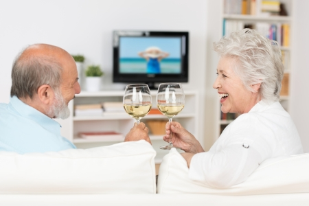 clinking: Senior couple celebrating with white wine clinking their glasses and toasting each other with a laugh as they sit on a sofa in their living room watching television Stock Photo