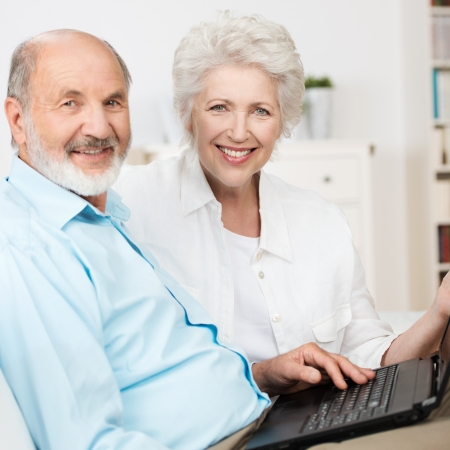 Elderly couple using a laptop computer as they sit side by side on a couch sharing the internet and smiling at the camera photo