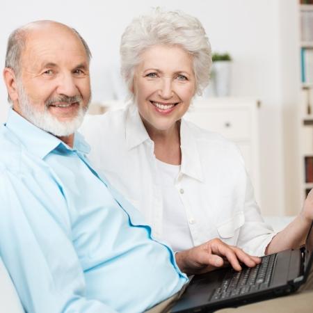 jubilados: Pareja de ancianos con un ordenador portátil, ya que se sientan de lado a lado en un sofá compartir el internet y sonriendo a la cámara Foto de archivo