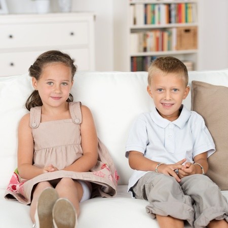 contented: Adorable beautiful little brother and sister sitting together quietly on a couch with their hands in their laps smiling at the camera