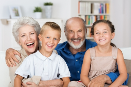 babysitting: Happy young boy and girl with their laughing grandparents smiling at the camera as they pose together indoors Stock Photo