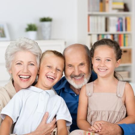 внук: Счастливый семейный портрет с любящим пожилая пара, обнимает их смех молодой внучку и внука, а создает в гостиной Фото со стока