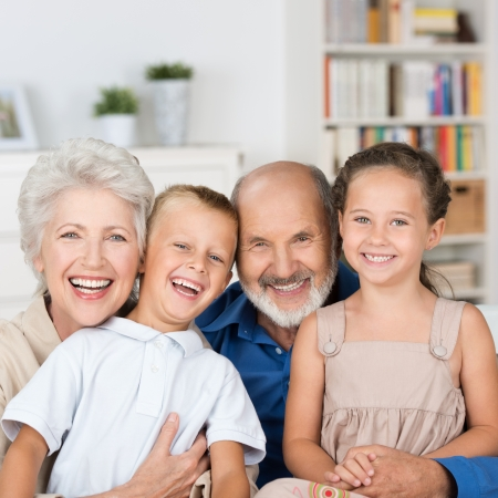 granddaughter: Happy family portrait with a loving elderly couple hugging their laughing young granddaughter and grandson while posing in the living room Stock Photo