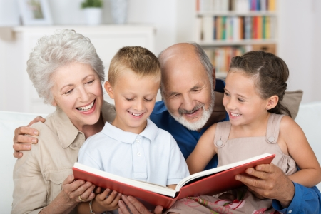 Cute boy and girl sitting in the lap of their grandparents and looking happily together at a photo album photo