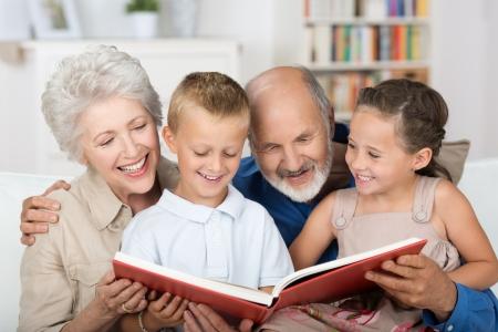 Netter Junge und Mädchen sitzen in den Schoß ihrer Großeltern und suchen glücklich zusammen in einem Fotoalbum