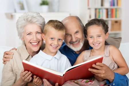 babysitting: Elderly couple reading to their grandchildren as they all sit close together on a sofa Stock Photo