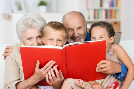 babysitting: Cute little boy and girl with merry smiling eyes reading with their grandparents peering over the top of the book at the camera