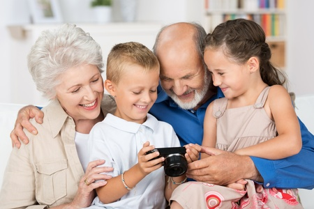 Two beautiful happy young grandchildren with their grandparents in a close group looking at the back of a camera at a photograph photo