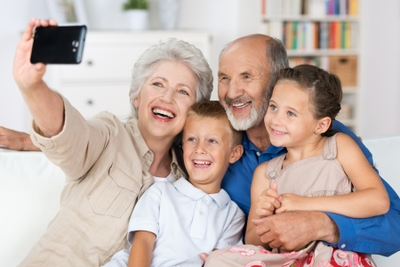 retirement: Grandparents and grandchildren sitting together in a close group on a sofa laughing and doing a self portrait with a hand held camera on a mobile phone Stock Photo