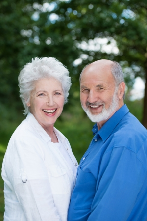 Joyful senior couple enjoying nature standing close together turning to look at the camera while laughing and smiling photo