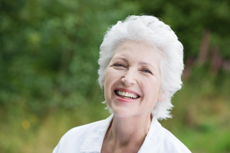 Vivacious laughing grey haired senior woman outdoors in a lush green park, close up portrait Stock Photo