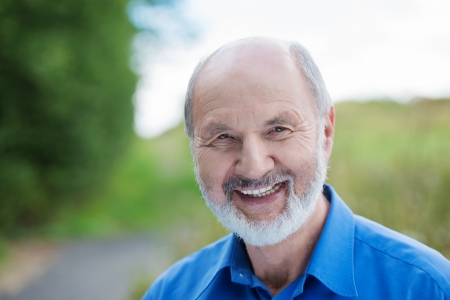 affable: Horizontal portrait of a happy Caucasian retired bearded man, outdoors with a blurred green area in the background