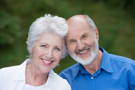 Portrait of a loving senior couple standing together outdoors facing the camera and smiling with their heads touching photo